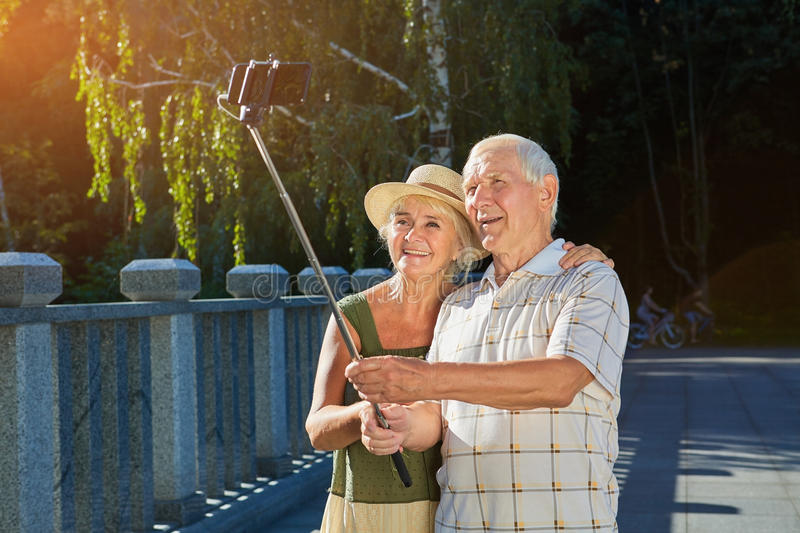 Old couple taking selfie outdoors. stock photo
