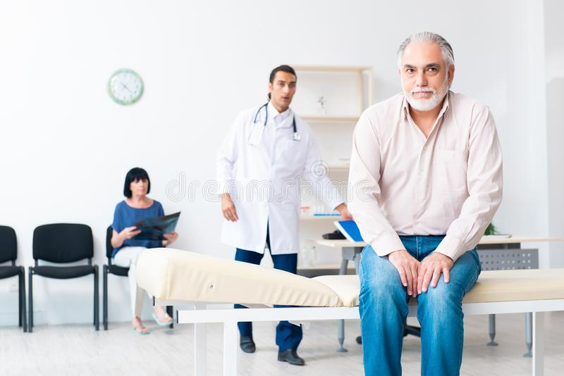 Old couple visiting young male doctor. The old couple visiting young male doctor royalty free stock photography