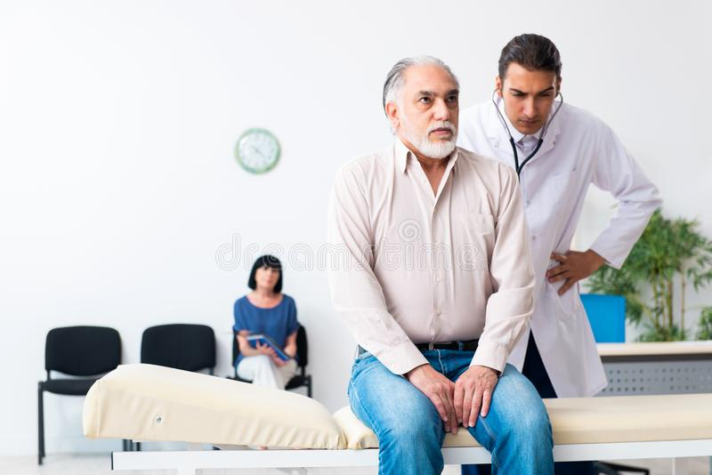 Old couple visiting young male doctor. The old couple visiting young male doctor royalty free stock images