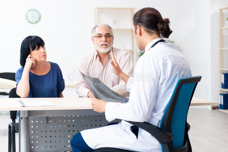 Old couple visiting young male doctor. The old couple visiting young male doctor stock image