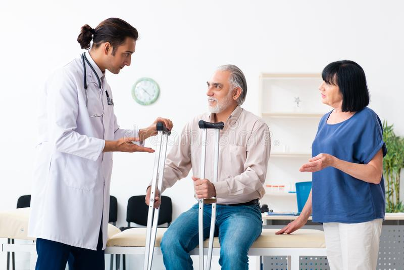 Old couple visiting young male doctor. The old couple visiting young male doctor royalty free stock photo
