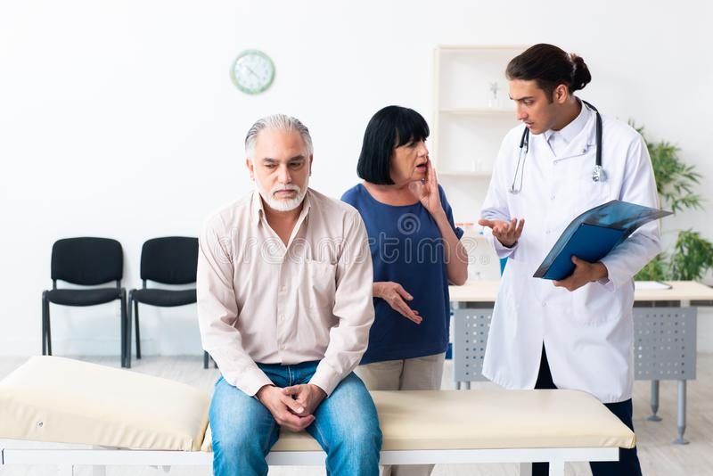 Old couple visiting young male doctor. The old couple visiting young male doctor stock photos