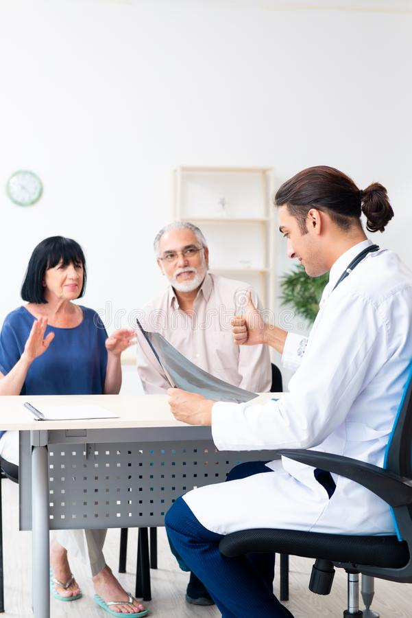 Old couple visiting young male doctor. The old couple visiting young male doctor royalty free stock image