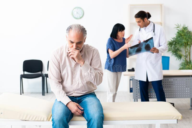 Old couple visiting young male doctor stock photo