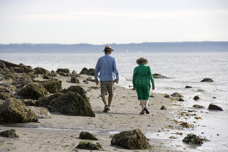 Old couple walking on beach stock images