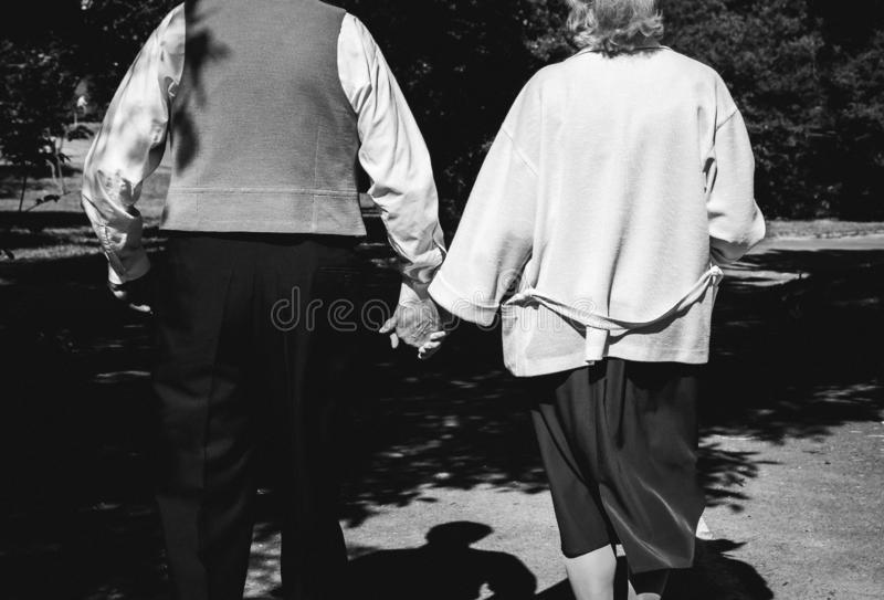 Old couple is walking in park. Grandmother and grandfather at golden wedding anniversary celebration. Fifty years love story. royalty free stock photos