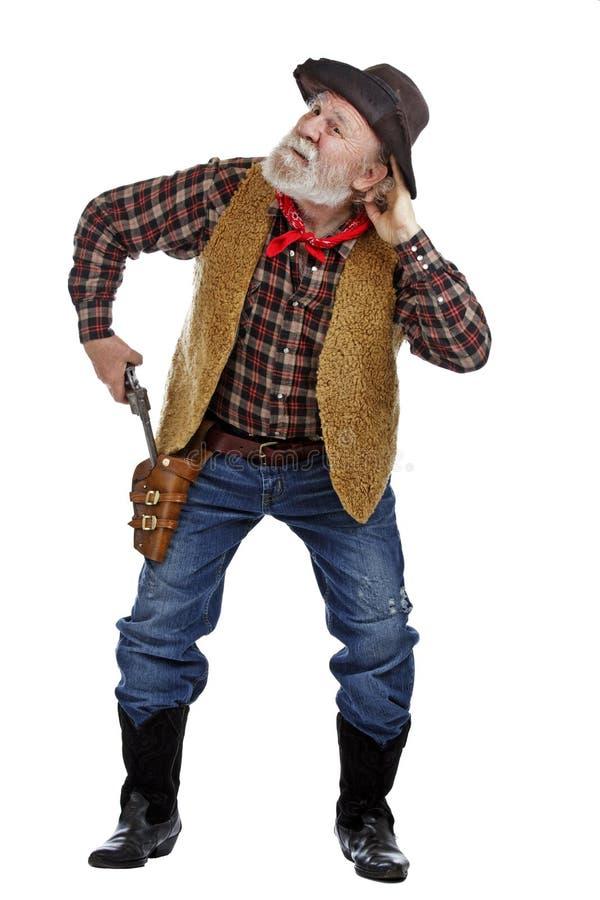 Old cowboy draws his gun and listens royalty free stock image