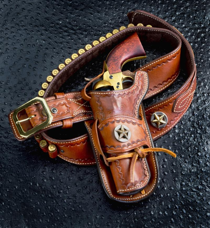 Old Cowboy Gun. Old cowboy 45 pistol and leather tooled holster royalty free stock image