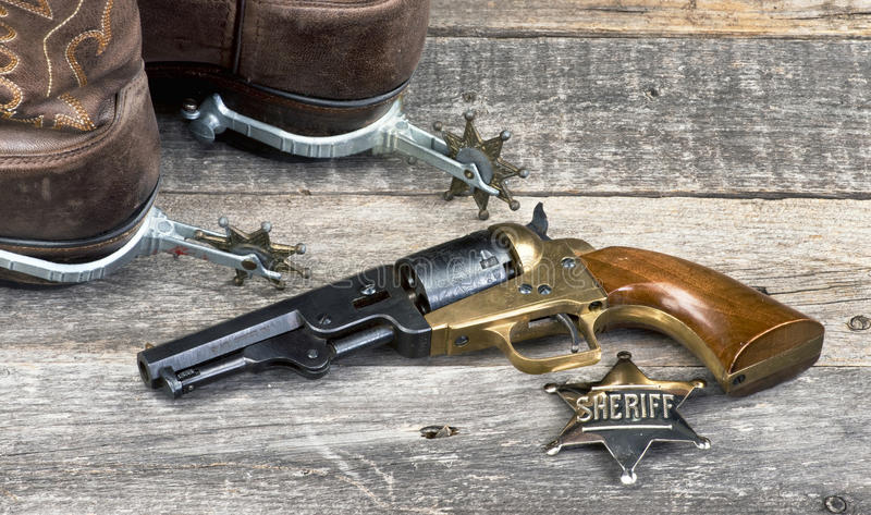 Old Cowboy Tools. Old western pistol, badge, spurs and cowboy boots royalty free stock photos