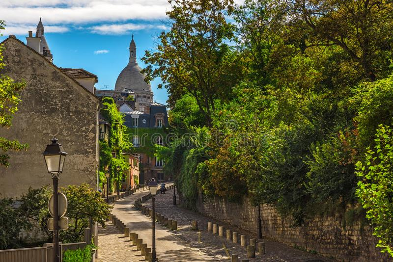Old cozy street in quarter Montmartre in Paris, France. Cozy cityscape of Paris royalty free stock photography