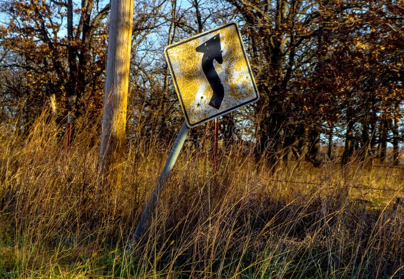 Old and cracked curve ahead sign tilting sideways along a country road in late afternoon with golden sun shinning on it and grass stock image
