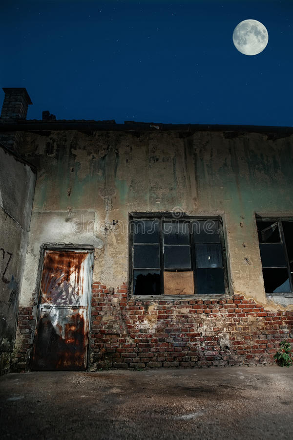 Old cracked or grungy place at background. Old house with brocken doors and windows. Moonlight royalty free stock images