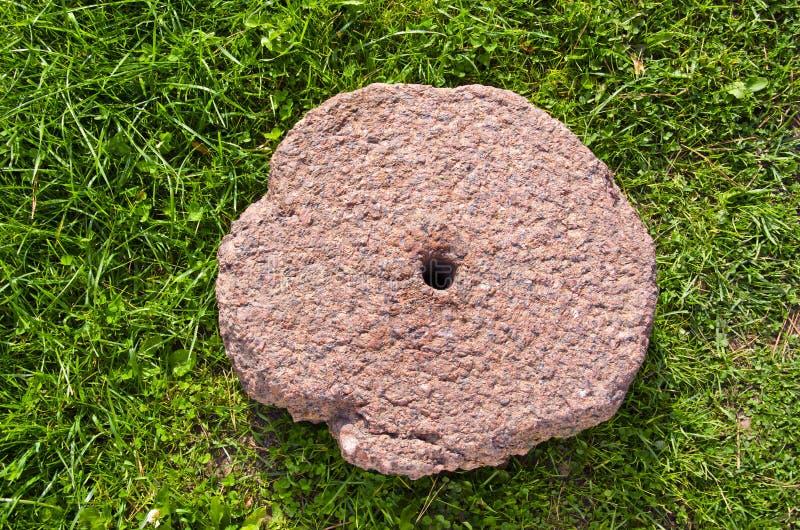 Old cracked millstone on grass stock photos