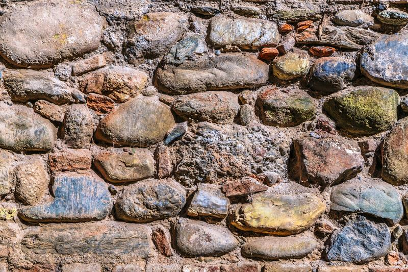 Old and cracked stone colored wall of some building. In Spain close up royalty free stock photography