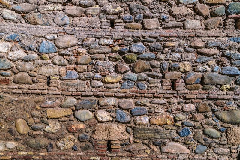 Old and cracked stone colored wall of some building. In Spain close up royalty free stock images