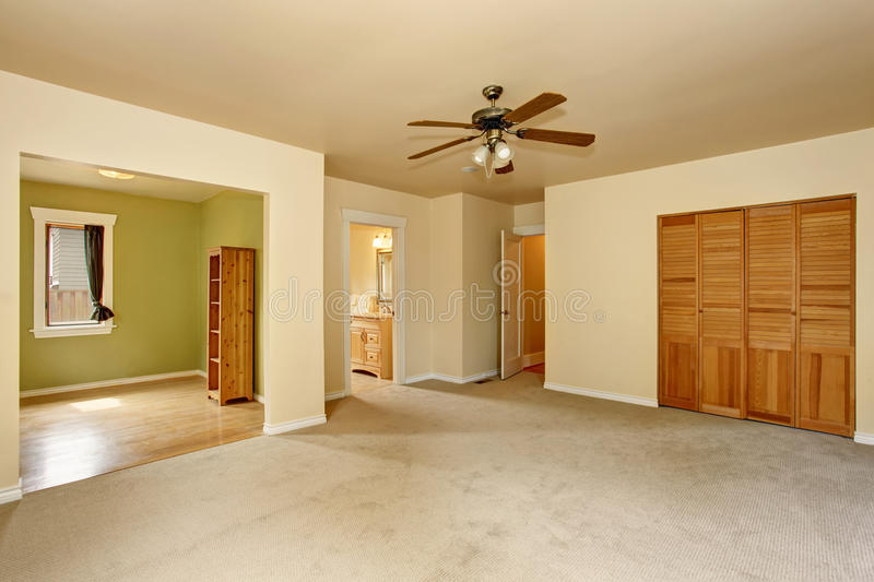 Old craftsman style house with beige interior paint. Carpet floor and built-in closet in empty room stock photography