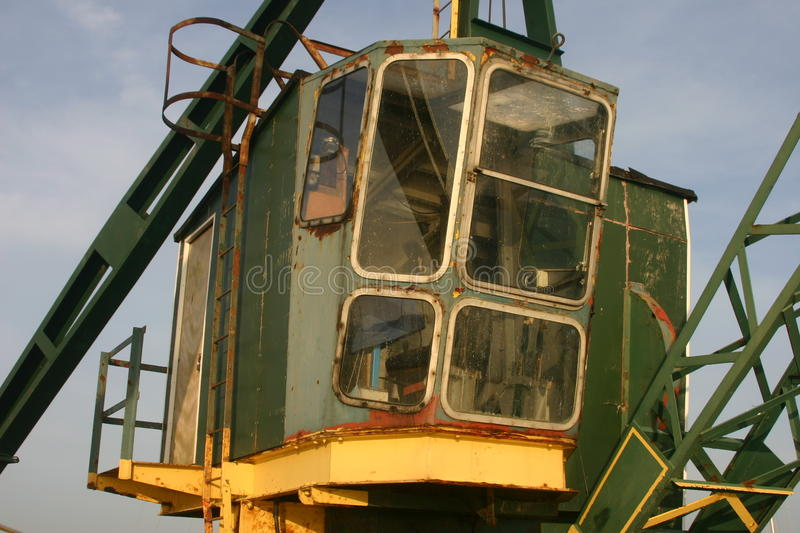 Old green crane. Old crane used to lift boats and goods alongside river. Green with yellow base and large front windows. Background is blue sky with white clouds royalty free stock photos