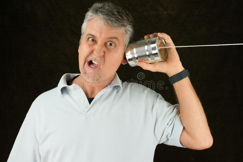 Old crappy antiquated technology funny frustrated man on tin can phone. Funny face frustrated man on tin can phone representing old, crappy, outdated, antiquated royalty free stock photos