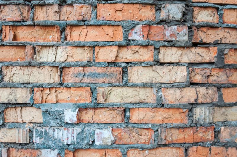 The old crashed wall of red brick with cement close-up. stock photo