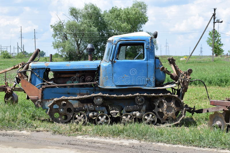 Old crawler tractor standing in a field. Old Kazakh crawler tractor standing in a field royalty free stock images