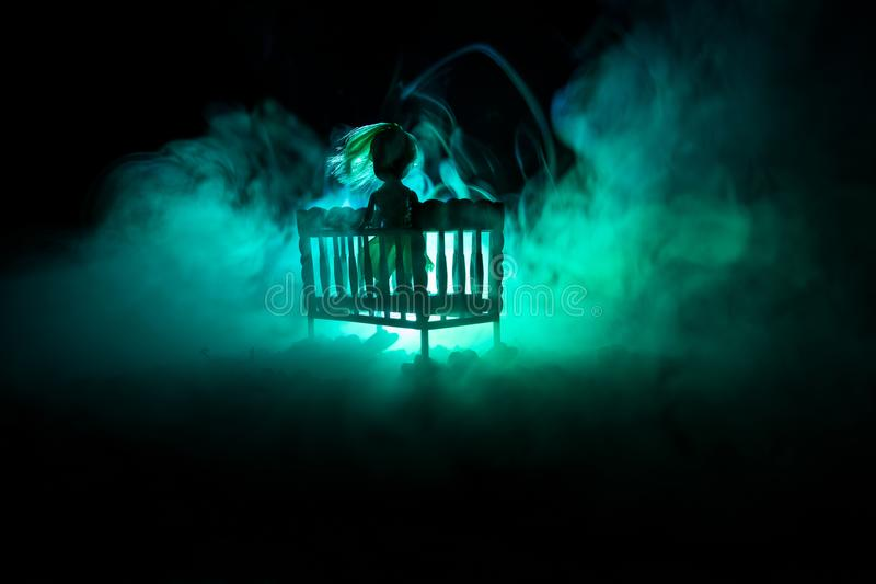 Old creepy eerie wooden baby crib in dark toned foggy background. Horror concept. Scary baby and bed silhouette in dark stock photography