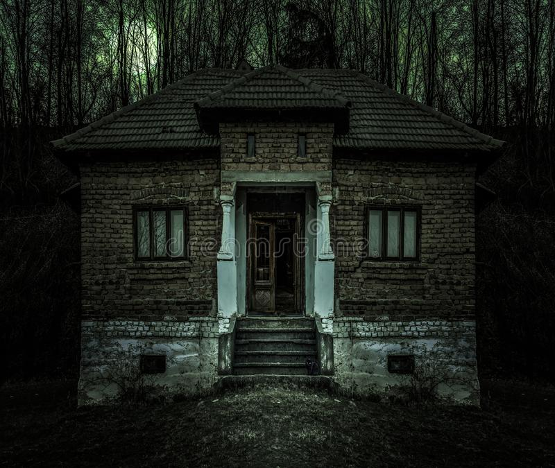 Old creepy haunted house with dark horror atmosphere and scary details. Ancient abandoned mansion with fool moon and black cat in. Frightening scene like in royalty free stock photos