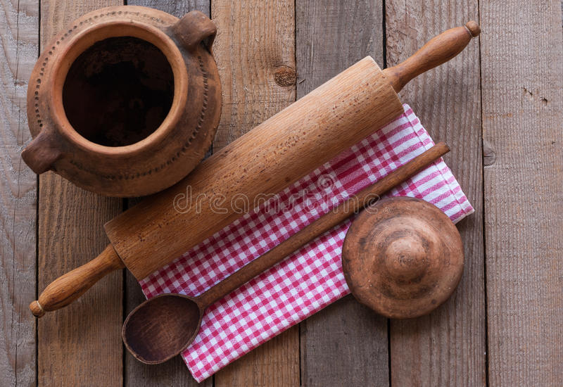 Old crock with rolling pin. On a wooden table stock photography