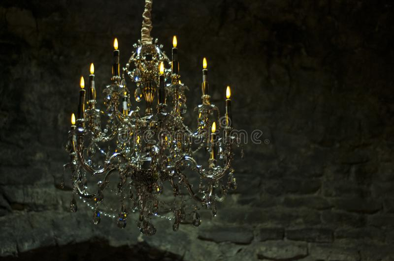 Old crystal chandelier with candles in a dark dungeon. Old brick walls. royalty free stock photo