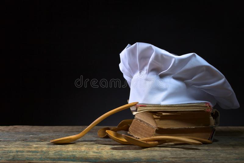 Old culinary books , chef hat and wooden spoons . Kitchen accessories on the old wooden table .Black background , copy space royalty free stock photography