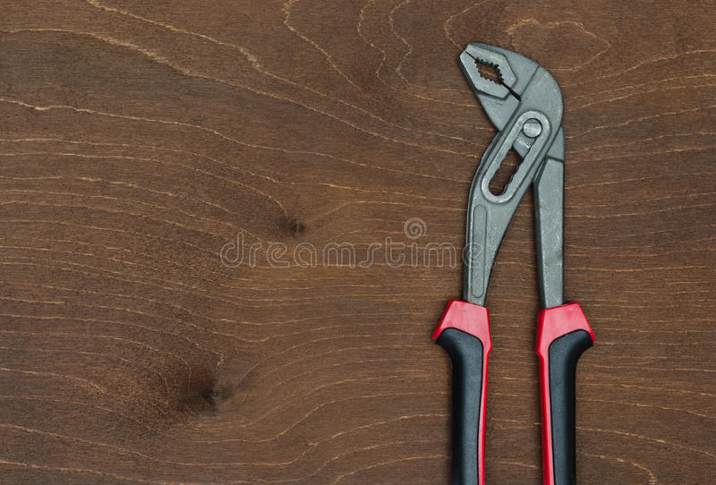 Old curved jaw pliers. On wooden table royalty free stock photos