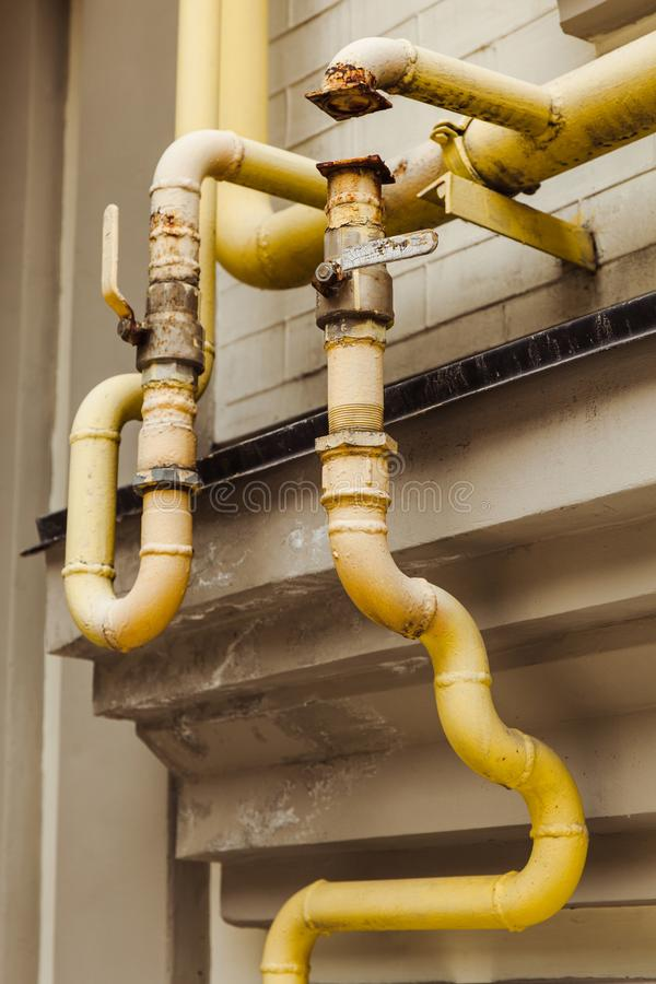 Old curved yellow pipes on the old house. stock image