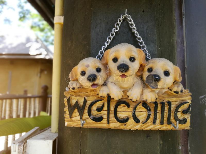 Old cute little dogs holding label write WELCOME out of home royalty free stock photo