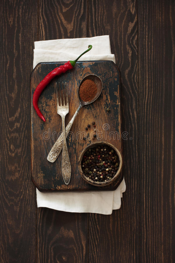 Old cutting board, peppers and vintage fork and spoon on a natura stock images