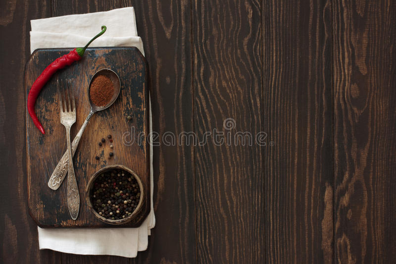 Old cutting board, peppers and vintage fork and spoon on a natura stock photos