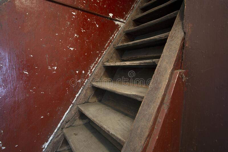 Old damaged brown wooden stairs and red wall leading to the attic, needs renovation stock photo