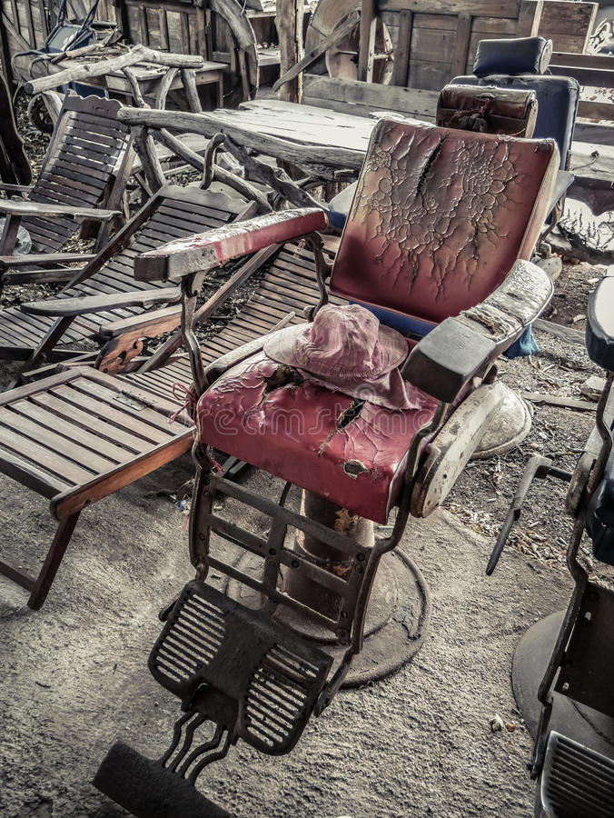 Old and damaged red barber chair and seat with cracked leather, flea market, junk shop royalty free stock image