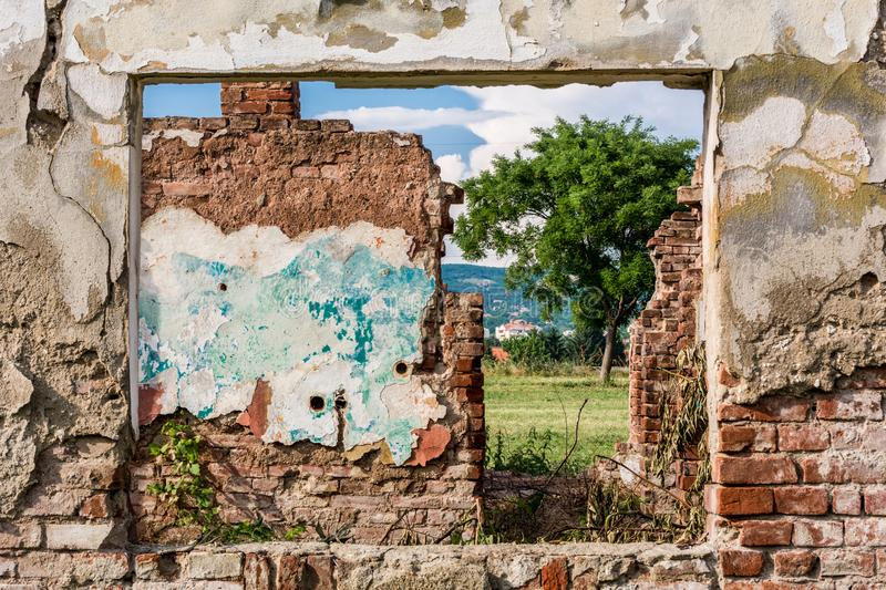 Damaged wall and window frame with view to ruins room and green field of grass stock photography