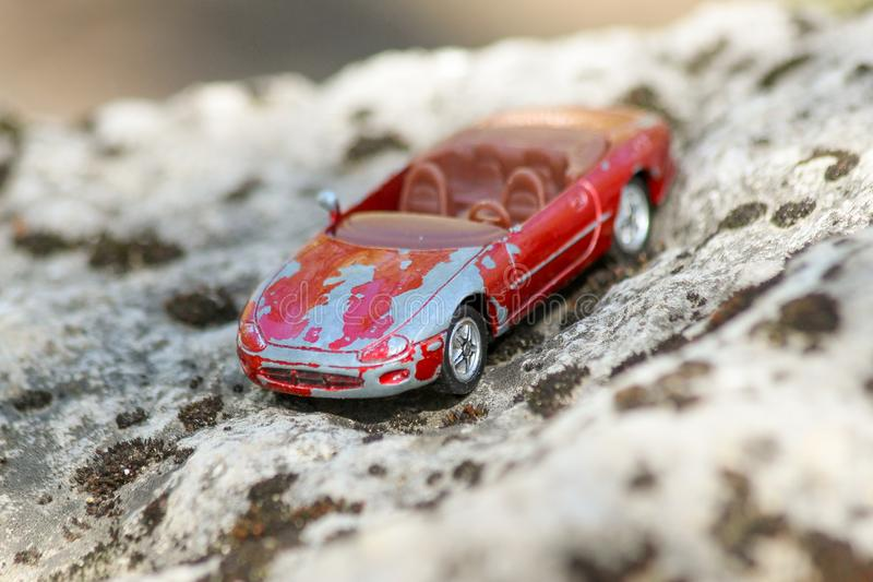 An old and damaged red toy car on a big stone covered with moss. Shallow depth of field royalty free stock image