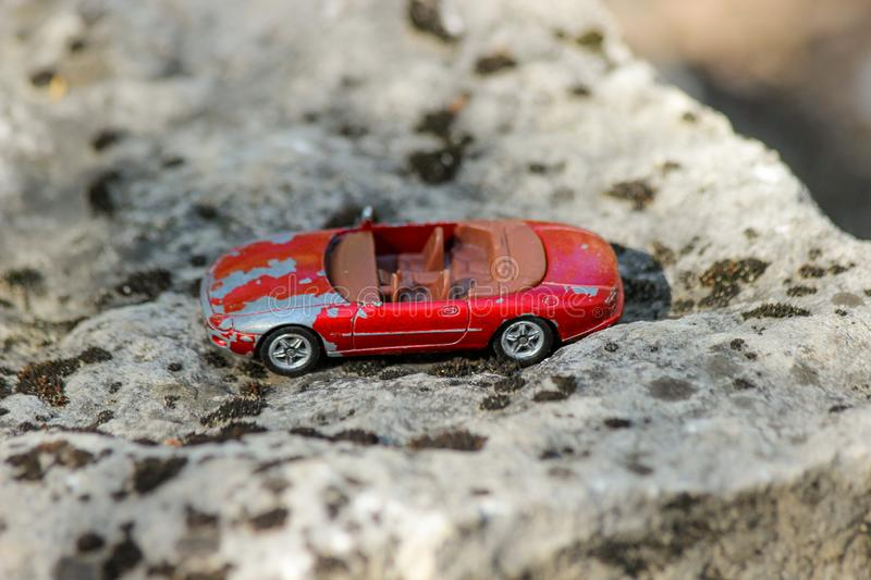 An old and damaged red toy car on a big stone covered with moss. Shallow depth of field stock images