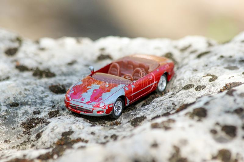 An old and damaged red toy car on a big stone covered with moss. Shallow depth of field stock image