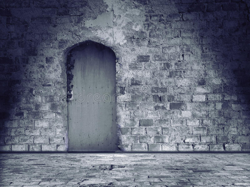 Old damaged stone wall and floor with closed door. Vintage background royalty free stock images