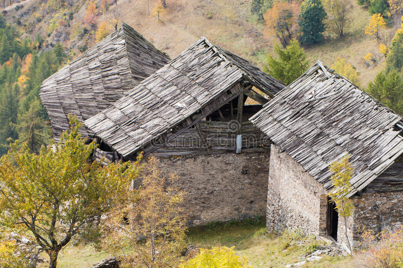 Old damaged wooden roofs of abandoned chalets in Italian Alps. Old damaged wooden roofs made of larch's planks covering three abandoned chalets in Italian Alps royalty free stock photography