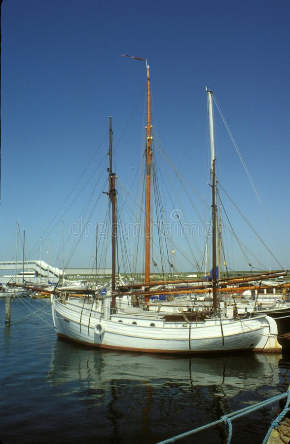 Old Danish white wooden sailboat. Ancient wooden Danish sailboat with two masts and clinker built hull in the port of Bagenkop, Langeland. Film photography stock image