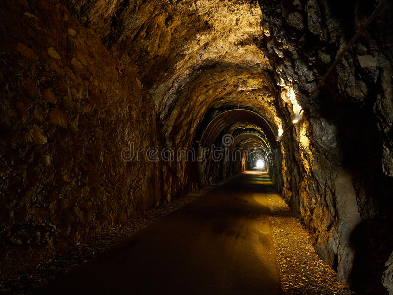 Old Dark Tunnel Dug in Stone. Day Light at the end. Old Dark Tunnel Dug in Stone. Day Light appears at the end stock photos