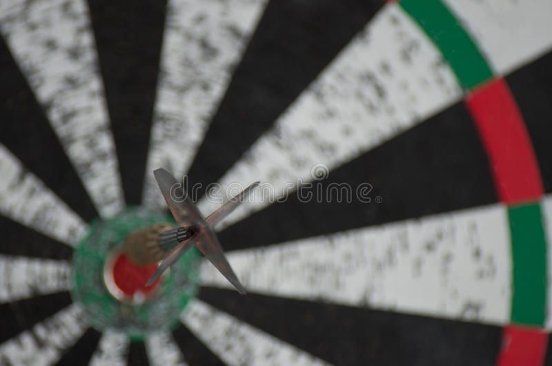 An old dartboard with a dart hit the bullseye stock image