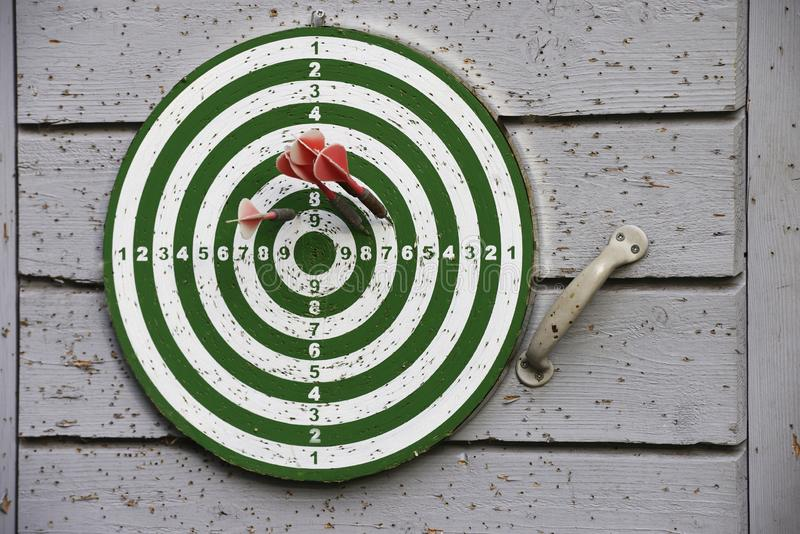 Old darts target hanging on the door outdoors stock images