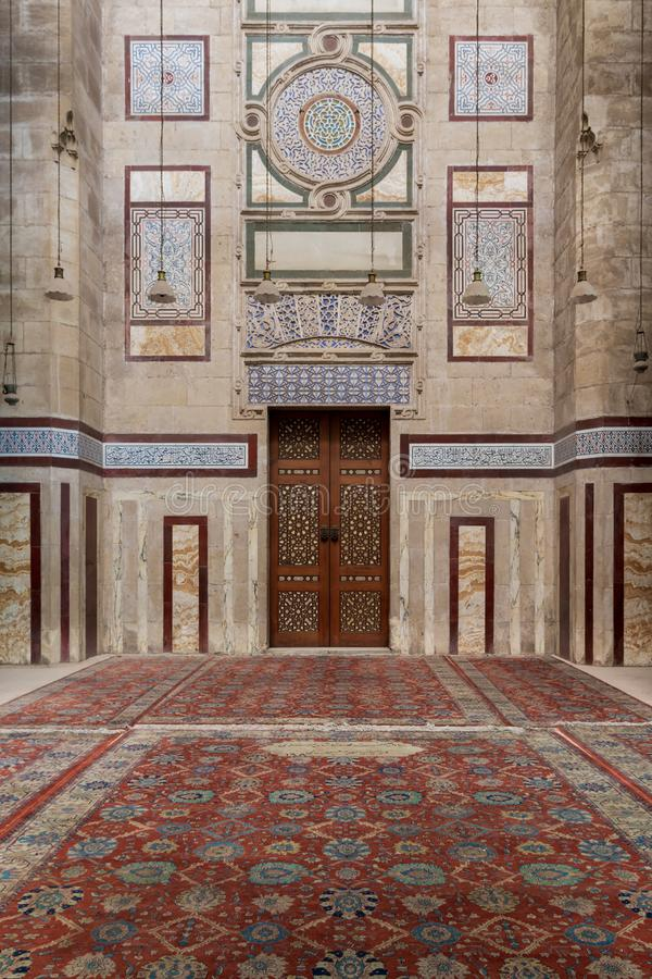 Old decorated stone wall, marble decorations and arabesque decorated wooden door, al Refai Mosque. Old decorated stone wall with marble decorations and arabesque stock photography
