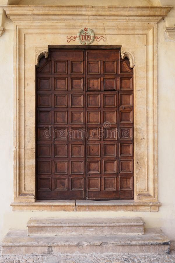 Old decorated wooden door of an Italian medieval church in Spello. stock image