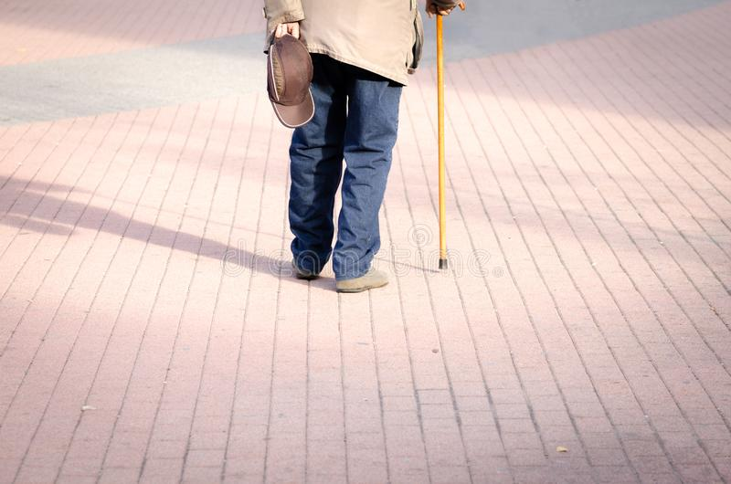 Old depressed man walk alone down the street with walking stick or cane feeling lonely and lost view from back stock images