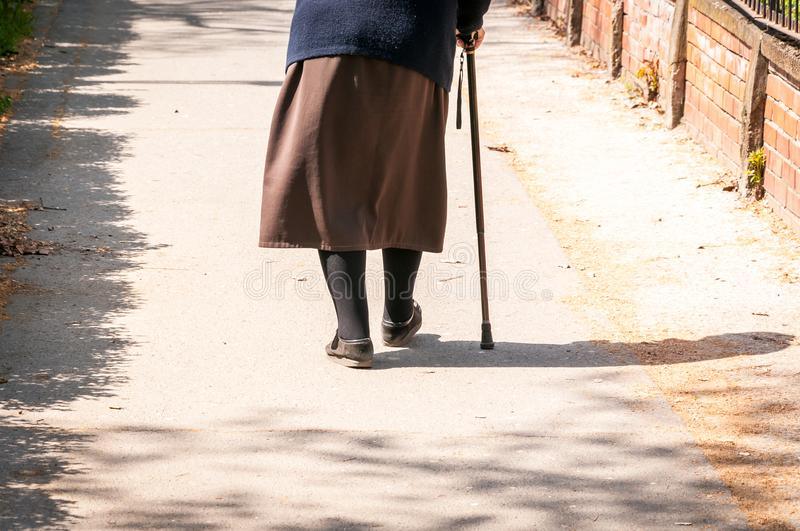 Old depressed woman walk alone down the street with walking stick or cane feeling lonely and lost view from back stock photo